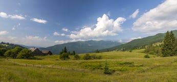 Case del villaggio sulle colline con i prati verdi nel giorno di estate Immagini Stock