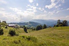 Case del villaggio sulle colline con i prati verdi nel giorno di estate Fotografie Stock Libere da Diritti