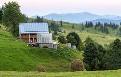 Case del villaggio sulle colline con i prati verdi nel giorno di estate Camera Immagini Stock Libere da Diritti