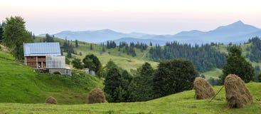 Case del villaggio sulle colline con i prati verdi nel giorno di estate Camera Immagine Stock Libera da Diritti