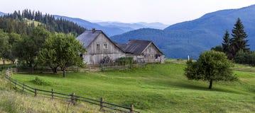 Case del villaggio sulle colline con i prati verdi nel giorno di estate Camera Fotografia Stock Libera da Diritti