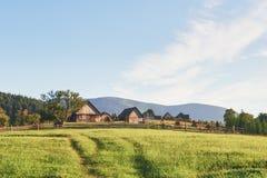 Case del villaggio sulle colline con i prati verdi nel giorno di estate Camera dei pastori in montagne in carpatico Immagini Stock