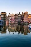 Case di Amsterdam con le facciate variopinte e barche giranti al canale del fiume di Amstel Fotografia Stock