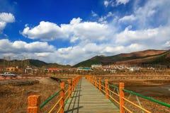 Case di campagna e ponte di legno alle colline pedemontana di una catena montuosa con cloudscape piacevole Fotografie Stock