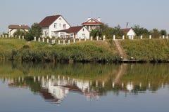 Case di campagna sulla sponda del fiume Immagine Stock