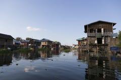 Case di legno del trampolo che riflettono nel villaggio del lago Inle, Shan State, Myanmar fotografia stock libera da diritti