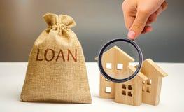 Case di legno e una borsa con il prestito di parola Acquisto della casa nel debito Concetto di investimento in immobili e della g immagini stock