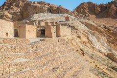 Case di pietra rovinate nel deserto contro il contesto delle alte montagne Fotografie Stock