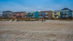 Case di spiaggia con la sabbia e l'erba e le nuvole di tempesta fotografia stock libera da diritti