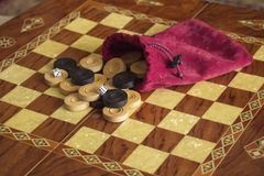Case with dice and checkers on a chess board stock photo