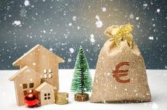 Case ed albero di Natale di legno e una borsa di soldi Vendita di Natale di Real Estate Sconti del nuovo anno per la casa d'acqui fotografie stock libere da diritti