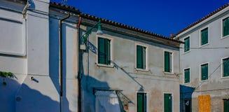 Case grige con le finestre verdi sull'isola di Burano, in Venic fotografia stock libera da diritti