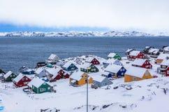 Case inuit variopinte fra le rocce e neve al fiordo in un sottomarino fotografia stock
