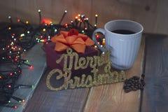 Case la Navidad y una taza azul de café y de una caja en la tabla Fotografía de archivo libre de regalías