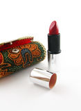 Case and lipstick. A case with ethnic pattern and an opened red lipstick on the white background Royalty Free Stock Image