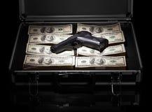 Case with money and gun Stock Photos