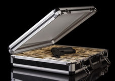 Case with money and gun. Silver case with money and gun on black background Stock Images