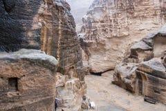 Case o tombe di pietra in rocce curve a pioggia persistente in poco PETRA - città antica di Nabatean fotografia stock