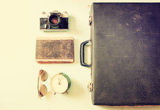 Case with old camera sunglasses and clock. filtered image. stock photos