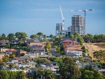 Case residenziali nel sobborgo del ` s di Melbourne con le nuove costruzioni di appartamento in costruzione nella distanza Fotografia Stock Libera da Diritti
