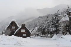 Case ricoperte di paglia del tetto coperte in neve nell'inverno Fotografia Stock