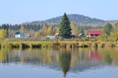 Case rurali sulla sponda del fiume Immagini Stock Libere da Diritti