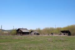 Case rustiche di legno abbandonate contro il cielo blu Fotografia Stock Libera da Diritti