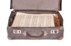Case with sheet music. A vintage case filled with vintage sheet music isolated on a white background Stock Photography