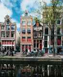 Case strette tipiche con le grandi finestre e canali con la riflessione, Amsterdam, Paesi Bassi Immagine Stock Libera da Diritti