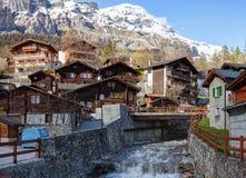 Case svizzere tipiche lungo il fiume di Dala un giorno di molla in Leukerbad, cantone del Valais, Svizzera Fotografia Stock