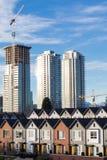 Case urbane nuovissime in una fila il giorno soleggiato luminoso con i Highrises nei precedenti Immagini Stock Libere da Diritti