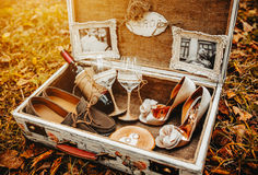 Case with wedding accessorize. Suitcase with different wedding accessories in the background leaves Stock Photography