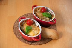 Caseiro julien com os cogumelos em dois vermelhos, bacias quentes Galinha com os cogumelos cozidos com queijo na tabela de madeir fotos de stock royalty free