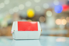 Casella con l'hamburger sulla tabella nel pasto rapido Immagine Stock