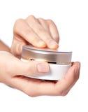 Casella crema sulla mano delle donne Fotografia Stock