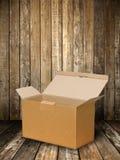 Casella di carta del Brown sul pavimento di legno Immagine Stock