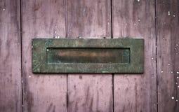 Casella di lettera arrugginita esposta all'aria su legno rosso Fotografia Stock Libera da Diritti