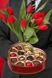 Casella e tulipani a forma di cuore della holding dell'uomo Fotografie Stock Libere da Diritti