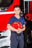Caserma dei pompieri felice di Holding Helmet At del pompiere fotografia stock
