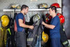 Caserma dei pompieri felice di Holding Jacket At del pompiere immagini stock