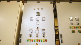 Cases with dashboard and danger warning sign at electrical station. Closeup white cases with dashboard and yellow danger warning sign for switchboards at stock video footage