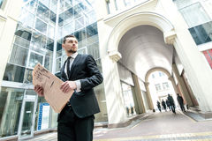 Cases made. Business man in formal wear standing downtown holdin Stock Photos