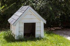 Caseta de perro de madera blanca en un patio trasero de la casa imagenes de archivo