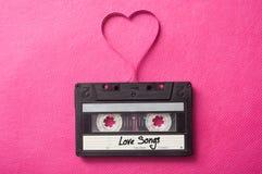 casete audio con canciones de amor del texto las 'con la banda magnética en corazón formado en fondo rosado imagen de archivo