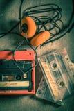 Casete audio con los auriculares y el walkman en la tabla gris Fotos de archivo