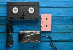 Casete audio, vhs, 3d vidrios, cámara de la película del inconformista en un fondo de madera amarillo Dispositivos retros de 80s  Imagen de archivo libre de regalías