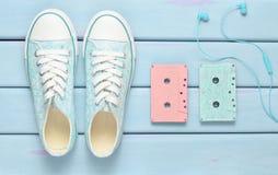 Casetes audios coloreados, auriculares, zapatos de las zapatillas de deporte en un fondo en colores pastel púrpura Tecnologías pa imagenes de archivo