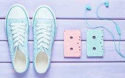 Casetes audios coloreados, auriculares, zapatos de las zapatillas de deporte en un fondo en colores pastel púrpura Tecnologías pa imagen de archivo
