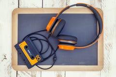 Casetes audios y auriculares del vintage sobre una pizarra negra foto de archivo libre de regalías