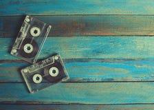 Casetes audios y auriculares en la superficie de madera azul Foto de archivo libre de regalías